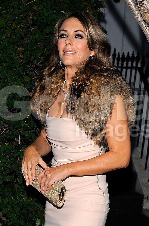 Actress Elizabeth Hurley returns home from filming The Royals and and makes a quick change into cream dress and fur shawl to attend the Woodside End Of Summer Party held in Windsor, London, UK. 04/09/2014<br />