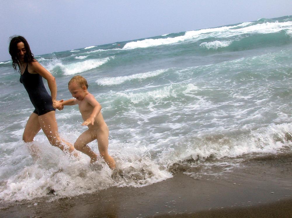 ITALIEN / Toskana.Toskanische Riviera - Ansedonia (Orbetello/Grosseto).Mutter mit Kind am Strand - Lauf durch die Brandung..07.07.2002..copyright > jungeblodt.com