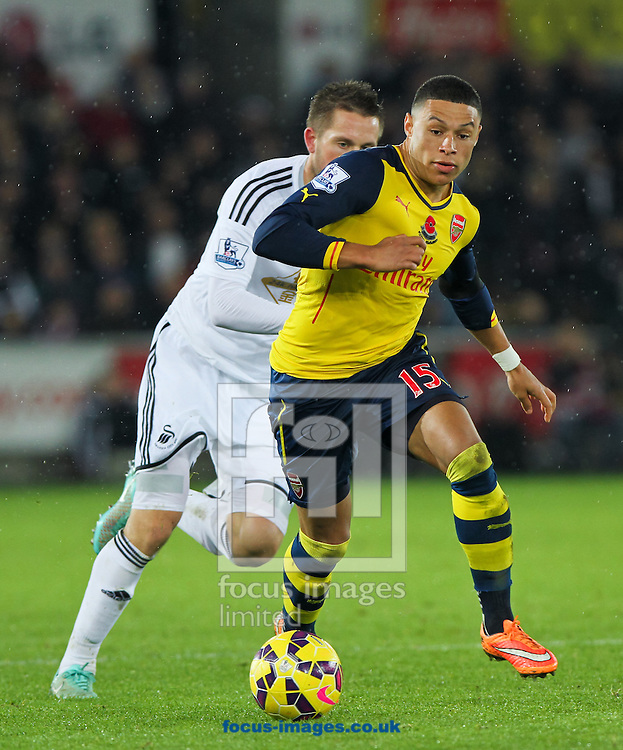 Alex Oxlade-Chamberlain (front) of Arsenal in possession of the ball during the Barclays Premier League match at the Liberty Stadium, Swansea<br /> Picture by Tom Smith/Focus Images Ltd 07545141164<br /> 09/11/2014