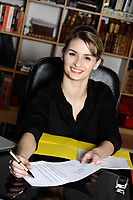 cute and smiling businesswoman at the office desk proposing you to sign a contract form