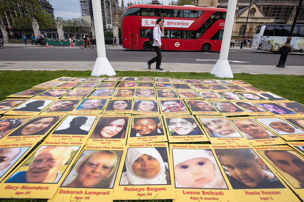 © Licensed to London News Pictures. 14/05/2018. London, UK. Photographs of the 71 victims of the Grenfell Tower fire are laid out on the floor at a protest in Parliament Square to mark eleven months since the tragedy. Photo credit: Rob Pinney/LNP