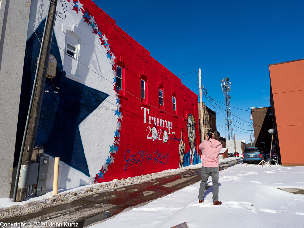 01 FEBRUARY 2020 - BOONE, IOWA: A man photographs a mural supporting President Donald Trump in downtown Boone, IA. Carl McKnight, a Boone realtor and Donald Trump supporter, commissioned the mural, which he calls nothing more than a campaign sign. Some in Boone, a community about 45 miles northwest of Des Moines, are concerned that the mural, which dominates a new park and bandshell in Boone, is not appropriate in a space shared by all people. A Boone city councilperson said people who donated to the fund to build the park have asked for their donations back. McKnight said the mural will stay up until at least election day.    PHOTO BY JACK KURTZ