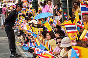 05 MAY 2010 - BANGKOK, THAILAND: A Thai police officer talks to people on the street in front of the Grand Palace in Bangkok waiting for Thai King Bhumibol Adulyade, Wednesday, May 5. Wednesday was Coronation Day in Thailand, marking the 60th anniversary of the coronation of Thai King Bhumibol Adulyade, also known as Rama IX. He is the world's longest serving current head of state and the longest reigning monarch in Thai history. He has reigned since June 9, 1946 and his coronation was on May 5, 1950, after he finished his studies. The King is revered by the Thai people. Thousands lined the streets around the Grand Palace hoping to catch a glimpse of the King as his motorcade pulled into the palace. The King has been hospitalized since September 2009, making only infrequent trips out of the hospital for official functions, like today's ceremonies.   PHOTO BY JACK KURTZ