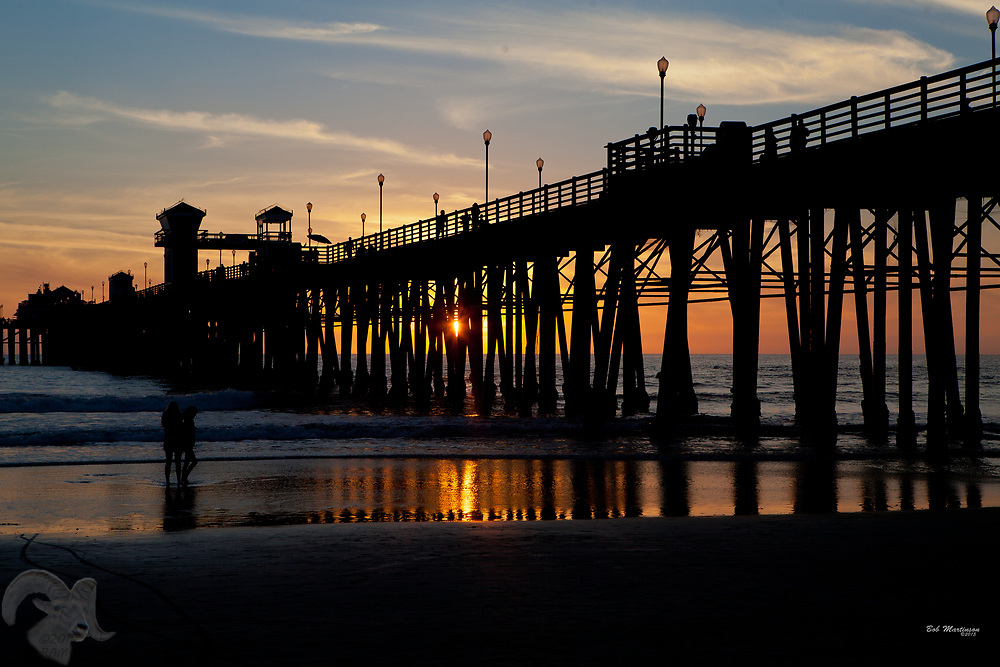 A couple walk on the beach as sunset shines through the Oceanside Pier in Oceanside, California.