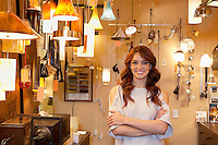Portrait of a beautiful young woman with arms crossed standing in lights store
