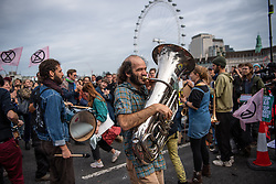 © Licensed to London News Pictures. 07/10/2019. London, UK. Extinction Rebellion (XR) activists are arrested on Westminster Bridge after bolting themselves to street furniture and makeshift obstacles. Photo credit: Guilhem Baker/LNP