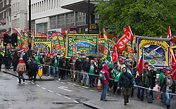 Occupy Wonga May Day. Protesters walk holding National Union banners towards Trafalgar Square on the annual May Day march. Central London, United Kingdom. Thursday, 1st May 2014. Picture by Daniel Leal-Olivas / i-Images