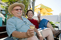 Senior couple sitting on bench and holding ice creams