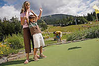 Mom and son enjoy a round of mini-golf at the Adventure Zone, Blackcomb Mountain, Whistler, BC Canada.