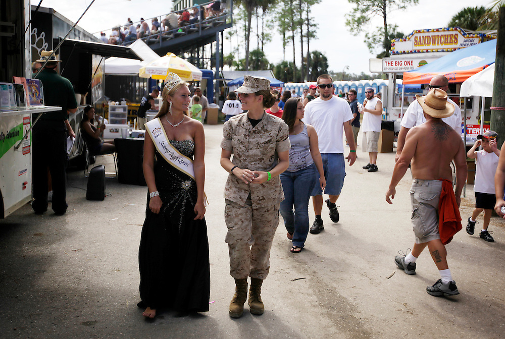 Pfc. Elaine Neal walks by food vendors with current Swamp Buggy Queen Megan Hoolihan, 18, left, as Neal helped with Marine recruiting at the Swamp Buggy races on Oct. 26, 2009. Neal said is was awkward at first to be in uniform at the Swamp Buggy Races, and wondered if people were curious at who the Marine was hanging out with the Hoolihan. Greg Kahn/Staff
