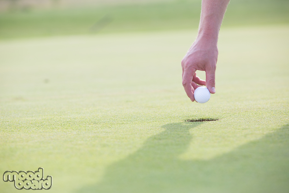 Cropped image of hand holding golf ball over cup