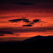 The glow of a dramatic red sunset over the skyline to the west of Athens, Greece.