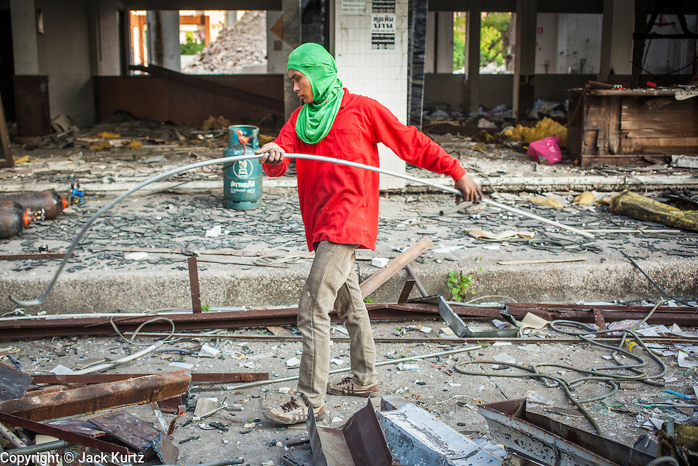 "13 DECEMBER 2012 - BANGKOK, THAILAND: A worker recycles metal in front of a building being torn down at ""Washington Square"" a notorious entertainment district off Sukhumvit Soi 22 in Bangkok. Demolition workers on many projects in Thailand live on their job site tearing down the building and recycling what can recycled as they do so until the site is no longer inhabitable. They sleep on the floors in the buildings or sometimes in tents, cooking on gas or charcoal stoves working from morning till dark. Sometimes families live and work together, other times just men. Washington Square was one of Bangkok's oldest red light districts. It was closed early 2012 and is being torn down to make way for redevelopment.    PHOTO BY JACK KURTZ"