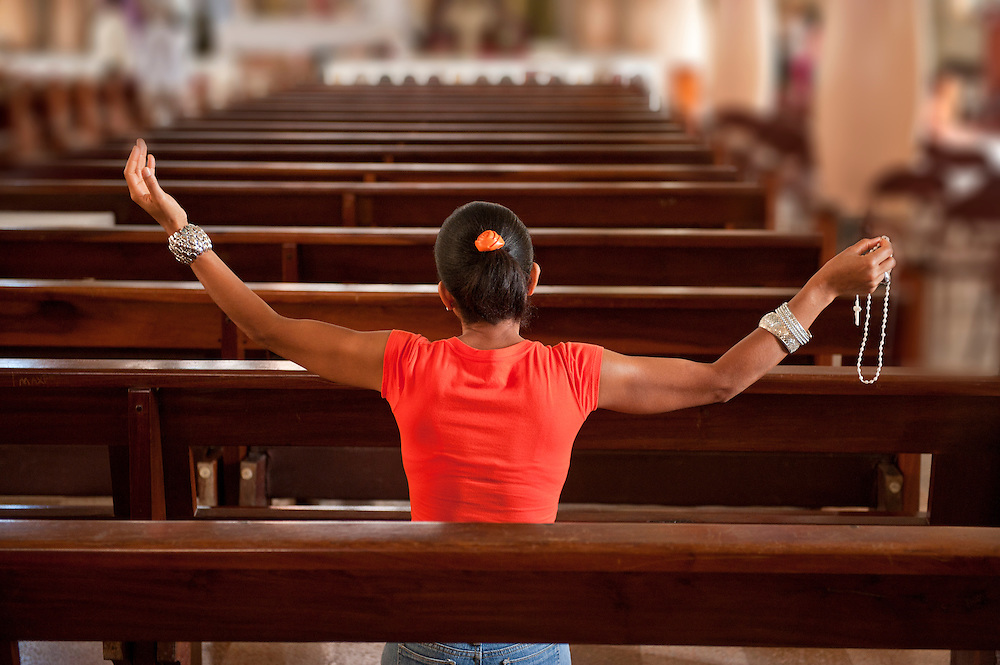 Woman praying in church, Moca,with rosary, Dominican Republic, Caribbean