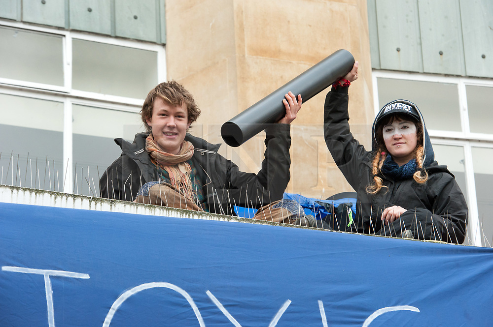 © Licensed to London News Pictures. 04/05/2017. Bristol, UK. Anti-fracking protest. Activists from 'Rising Up' lock themselves together with their arms in a tube on top of Barclays Bank in Broadmead shopping centre. Police removed the two protestors with help from the fire brigade's turntable ladder, and both rooftop protestors were arrested plus another person was arrested on suspicion of writing slogans using chalk on the pavement. The protest is a prelude to Global Divestment in Fossil Fuels day on Friday 05 May and 06 May. Photo credit : Simon Chapman/LNP