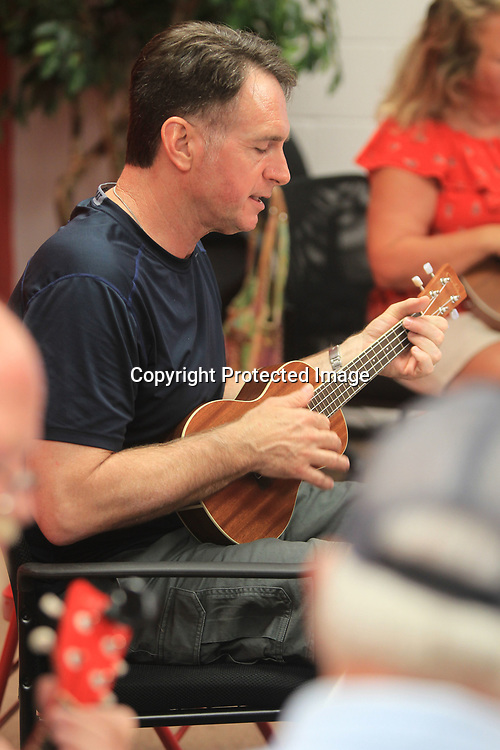Jeff Houin, of Tupelo, reads the sheet music as she practices a Red Hot Chili Peppers song on Ukulele with the others in the group.
