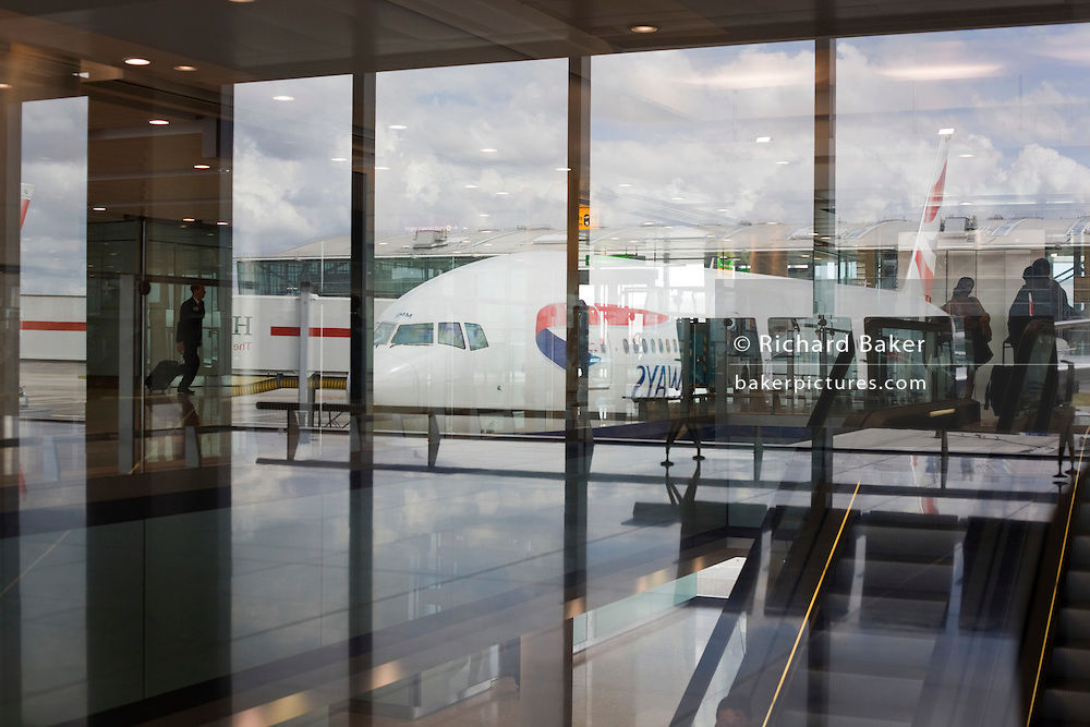 Arriving passengers, British Airways aircraft and airport architecture at Heathrow's Terminal 5.
