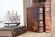 Old rare leatherbound books on a bookshelf with a model of a tall ship