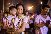 "25 FEBRUARY 2013 - BANGKOK, THAILAND: A woman and her son participate in a procession around Wat Benchamabophit Dusitvanaram (popularly known as either Wat Bencha or the Marble Temple) on Makha Bucha Day. Thais visit temples throughout the Kingdom on Makha Bucha Day to make merit and participate in candle light processions around the temples. Makha Bucha is a Buddhist holiday celebrated in Myanmar (Burma), Thailand, Cambodia and Laos on the full moon day of the third lunar month (February 25 in 2013). The third lunar month is known in Thai is Makha. Bucha is a Thai word meaning ""to venerate"" or ""to honor"". Makha Bucha Day is for the veneration of Buddha and his teachings on the full moon day of the third lunar month. Makha Bucha Day marks the day that 1,250 Arahata spontaneously came to see the Buddha. The Buddha in turn laid down the principles his teachings. In Thailand, this teaching has been dubbed the 'Heart of Buddhism'.      PHOTO BY JACK KURTZ"
