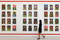 © Licensed to London News Pictures. 12/09/2018. LONDON, UK. A staff member passes works by Johnson Weree (Liberia) at the preview of START, a contemporary art fair comprising eclectic works from a variety of international emerging artists.  The fair takes place at the Saatchi Gallery in Chelsea 13 to 16 September 2018.  Photo credit: Stephen Chung/LNP