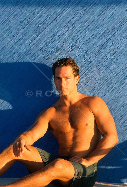Toned man against a blue wall