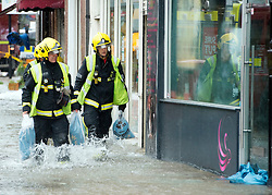 © Licensed to London News Pictures. 06/10/2014. Twickenham, UK. Firefighters use sandbags to help shopkeepers.  Firefighters help to contain a mains water pipe which has burst in King Street Twickenham today 6th October 2014. It appears that workmen working in the area have used a JCB digger to stem the flow. Many local shops and businesses have been flooded.   Photo credit : Stephen Simpson/LNP