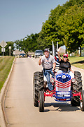 "08 AUGUST 2020 - WEST DES MOINES, IOWA: GARY LEFFLER, from West Des Moines, and TANA GOERTZ, drive a red, white, and blue tractor down Mills Civic Parkway during a rally to support law enforcement in West Des Moines. About 100 people gathered at the West Des Moines Law Enforcement Center to rally in support of law enforcement. The rally was organized by ""Uplifting Our Police,"" a local organization that supports law enforcement. They rallied at Des Moines Police headquarters in July. They are planning similar rallies at police stations in the Des Moines metropolitan area.      PHOTO BY JACK KURTZ"