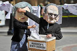 © Licensed to London News Pictures. 12/09/2017. London, UK. A couple stand outside the Houses of Parliament wearing a papier mache head mask of Theresa May and Rupert Murdoch as Karen Bradley, Culture Secretary, announces that she will refer 21st Century Fox's GBP11.67bn bid to buy Sky to competition regulators on the grounds of media plurality and broadcasting standards. Photo credit : Stephen Chung/LNP