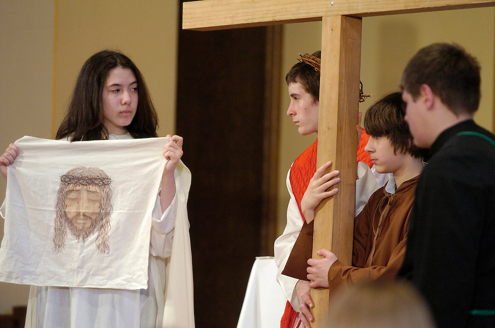 Veronica, portrayed by eighth grader Jana Rodriguez, holds a cloth with the image of Jesus, who is played by Nicholas Reinhold. Eighth grade students at St. Richard School in Racine, Wis., prepare to re-enacted the living Stations of the Cross for fellow students on Holy Thursday. (Catholic Herald photo by Sam Lucero)