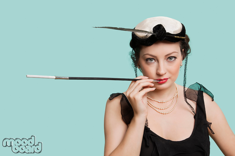 Portrait of happy young woman holding old-fashioned cigarette holder against blue background