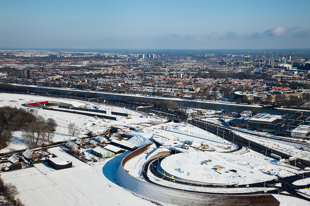 Nederland, Utrecht, Leidsche Rijn, 31-01-2010; het nieuwe knooppunt Hooggelegen met op het tweede plan de zuidelijke ingang van de nieuwe landtunnel voor de A2. De tunnel ligt parallel aan de bestaande A2, het asfalt zal op termijn verdwijnen en op het dak van de tunnel zal een park komen. Rechts het Amsterdam-Rijnkanaal..The new junction Hooggelegen and behind it the southern entrance of the new landtunnel for A2. The tunnel lies parallel to the existing motorway A2, the asphalt will eventually disappear and the roof of the tunnel will be a park. Left of the tunnel Leidsche Rijn with the districts and Langerak Parkwijk. Right the Amsterdam-Rhine Canal.luchtfoto (toeslag), aerial photo (additional fee required).foto/photo Siebe Swart