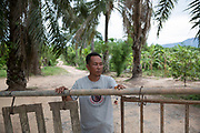 Tawat Ruangsi, 48, stands at the main entrance and security post to Klong Sai Pattana village after having just closed the gate at 6pm. The village tries to limit the number of vehicles entering and leaving during the night and re-opens at 6am. In total the village has 4 security posts which are manned 24 hours a day by the villagers who take it in turn in small groups of 3-4 people.<br /> <br /> Since 2008, this community of around 70 families have been embroiled in a conflict with a palm oil company that locals allege has been trying to violently evict them. Since 2010, four members of the community have been shot dead and a fifth shot, but survived.<br /> <br /> For decades the palm oil company Jiew Kang Jue Pattana Co., Ltd has illegally occupied and cultivated palm oil trees on a 535-acre plot of land in the Chai Buri District of Surat Thani Province. <br /> <br /> The company operated with no official legal documentation or land concession, until the Southern Peasant's Federation of Thailand (SPFT), who supports the community, began investigating them and collecting evidence.<br /> <br /> This evidence ultimately lead to a Supreme Court ruling against the company for illegal trespassing and land encroachment. But the community still struggles to remain on the land to this day with the last shooting happening in April 2016, years after the court case was won.