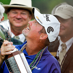 2009 April 26: PGA Tour golf pro Jerry Kelly tries to catch rain the Zurich Classic of New Orleans championship trophy after it began to rain during the award ceremony after winning the tournament's final round at TPC Louisiana in Avondale, Louisiana.