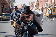 A veiled woman and a man on motor scooters on a street in Marrakesh, Morocco.  Urban scene for editorial use. Not model released.