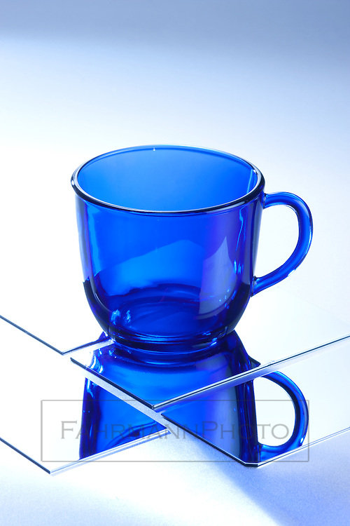 An empty cobalt blue coffee cup sits atop highly polished reflective metal surface.