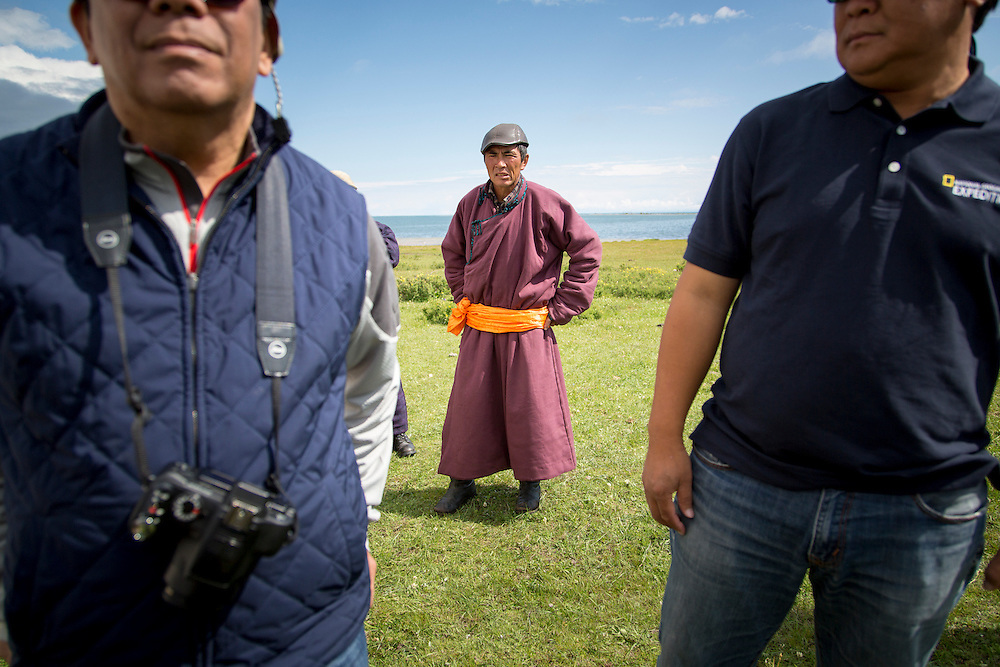A Mongolian man wearing a traditional Mongolian deel stands on the shore of Lake Hovsgol after erecting a traditional Mongolian Ger at on July 24, 2012.  © 2012 Tom Turner Photography