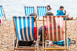 © Licensed to London News Pictures. 14/07/2019. Brighton, UK. A handful of visitors brave the grey and cloudy weather to spend time on the beach in Brighton and Hove. Photo credit: Hugo Michiels/LNP