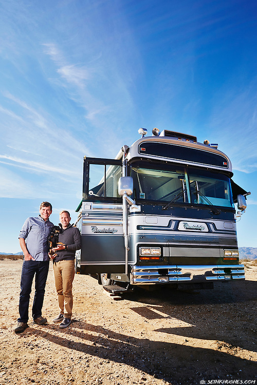 Full-time RV travelers stand next to their 1986 Wanderlodge Class A coach.