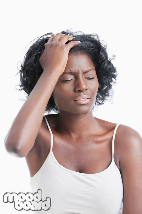 An African American young woman suffering from headache over white background
