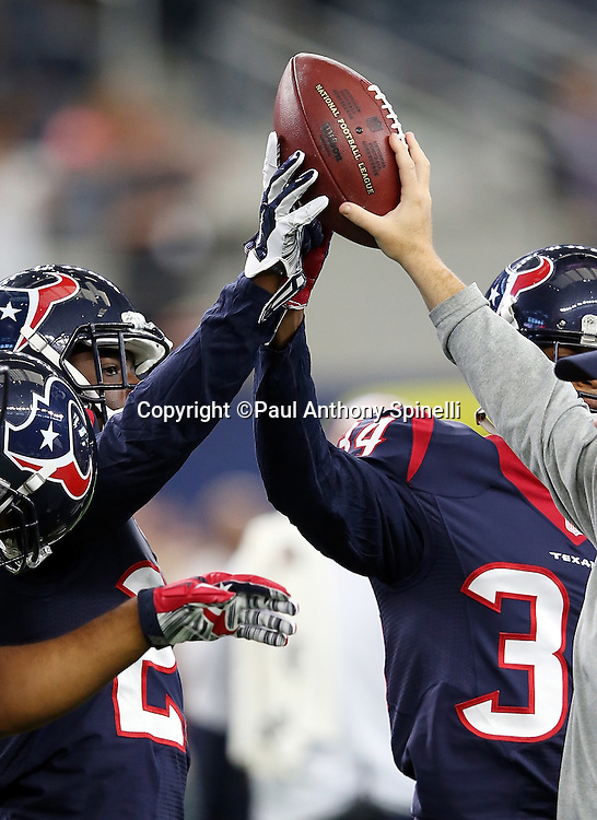 The Houston Texans hold a ball in the air before the 2015 NFL preseason football game against the Dallas Cowboys on Thursday, Sept. 3, 2015 in Arlington, Texas. The Cowboys won the game 21-14. (©Paul Anthony Spinelli)