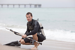 good looking underwater diver holding a speargun while on the shore of the beach in Florida