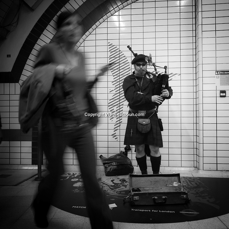 London. UK - scotish musician in traditional dress playing pipe in the subway of london
