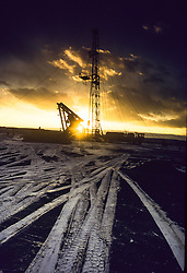 sun rising behind an on-shore rig