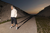 Mid adult man wearing hooded sweatshirt standing in middle of deserted road evening
