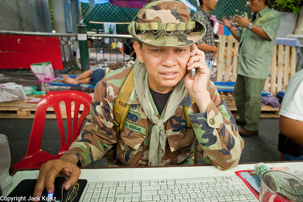"May 12 - BANGKOK, THAILAND: Maj. Gen. KHATTIYA ""Seh Daeng"" SAWASDIPOL uses a cell phone and computer to stay in touch with Red Shirt barricades in the Red Shirt camp in Bangkok Wednesday. Seh Daeng, as he is known, has emerged as the Red Shirts unofficial military commander. He has organized the barricades that ring the Red Shirt camp and has threatened to organize a guerilla campaign against the government if the Red Shirt protest is crushed by force. Seh Daeng is a hero to many Thais because he is credited with crushing Thailand's communist insurgency in the 1970's and 80's. He was the commander of Thailand's Internal Security Operations Command but after his political activities became apparent he was made the head aerobics instructor for the Thai army. He is now seen as one of the major personalities destabilizing the country and the government alleges that he is behind many of the grenade attacks and drive by shootings directed at government buildings and officials and he is wanted for a long list of felony offenses including weapons charges and terrorism related charges. Although some Red Shirts have officially repudiated him, he is still frequently seen around the Reds' barricades. The army has started proceedings to fire him, but he remains a general on active duty.   Photo by Jack Kurtz"