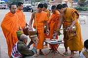 A man is making an offering of rice to Buddhist monk's during morning alms on a city street in Pakse, Laos.