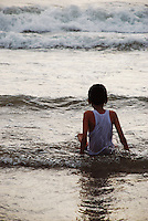 Small boy sitting in the surf watching the waves come in, Bali, Indonesia.