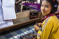 MANDALAY, MYANMAR - CIRCA DECEMBER 2013: Young woman working webing typical Burmese fabrics in Amarpura in Myanmar