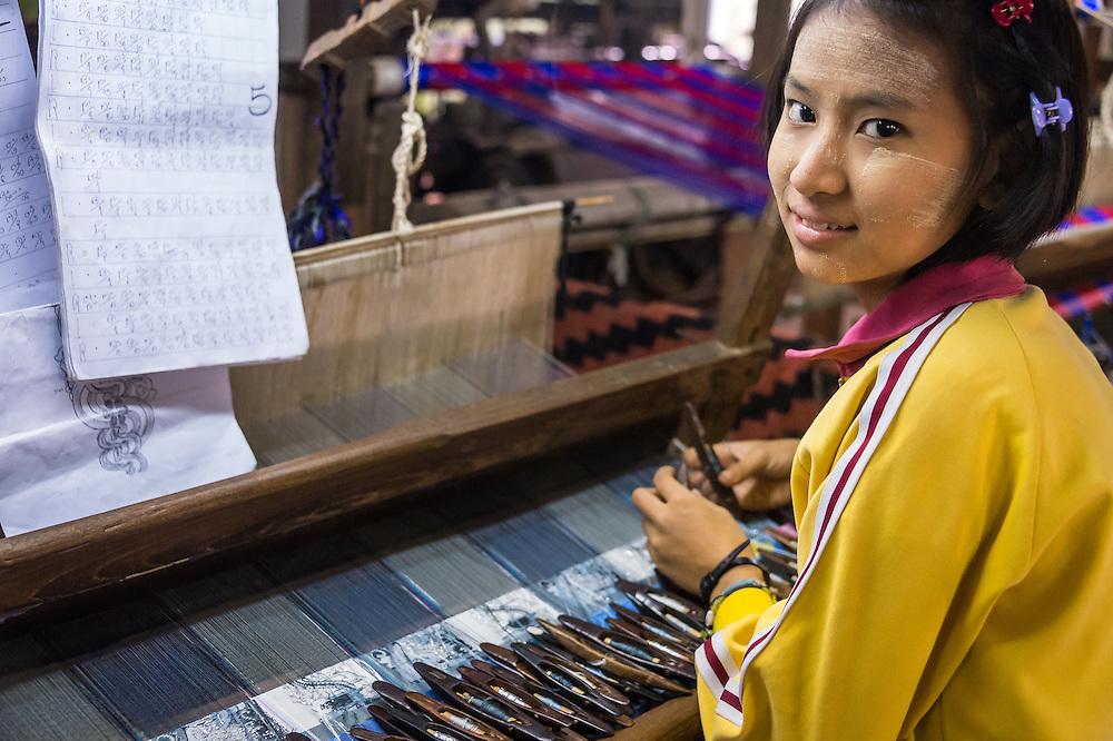 MANDALAY, MYANMAR - CIRCA DECEMBER 2013: Young woman working webing typical Burmese fabrics in Amarpura in Myanmar