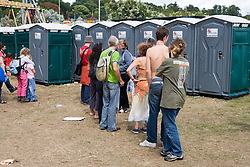 Men and women queuing at the portaloos at the WOMAD (World of Music; Arts and Dance) Festival in reading; 2005,